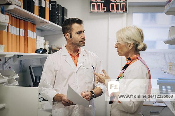 Reife Mediziner diskutieren im Apothekenladen über Dokumente per Regal