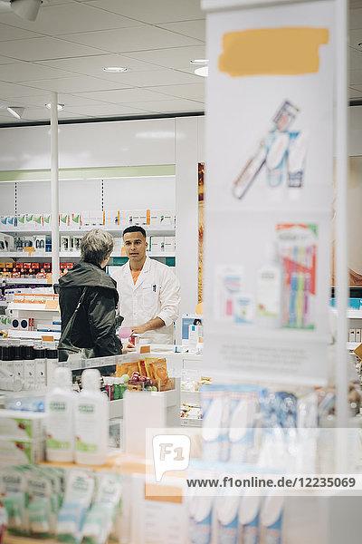 Senior Kundin im Gespräch mit Apothekerin an der Kasse im Geschäft