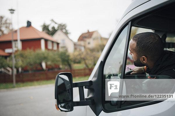 Mann im Lieferwagen in der Stadt sitzend