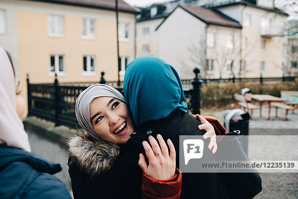Happy young female friends embracing in city