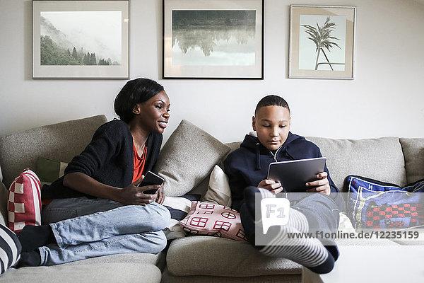 Volle Länge der Mutter  die den Sohn mit einem digitalen Tablett auf dem Sofa zu Hause betrachtet.