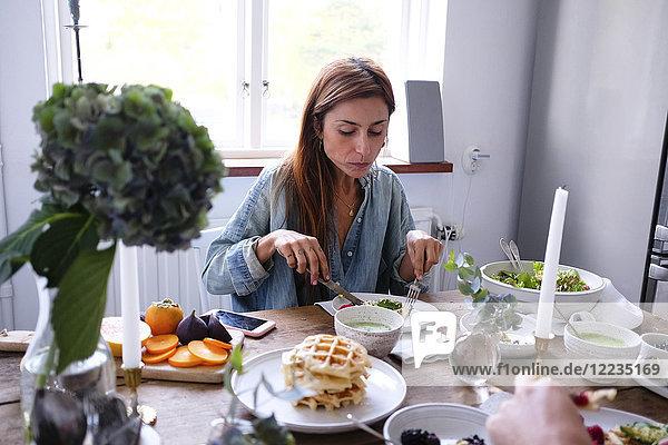 Paar mit Essen am Tisch gegen das Fenster