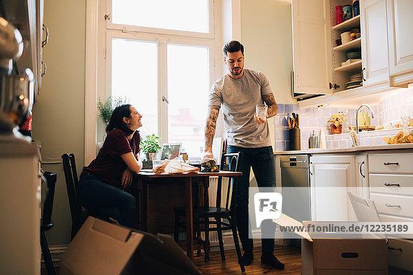 Lächelnde Frau schaut Mann mit Glas in der Küche an