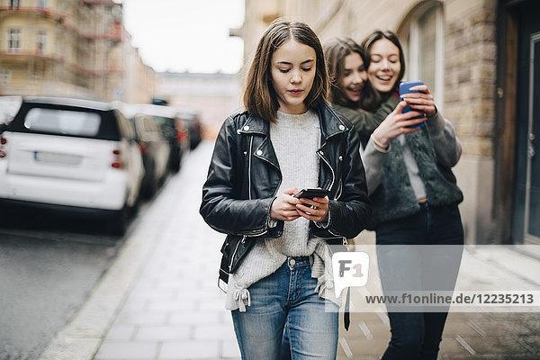 Weibliche Freunde beim Gehen auf dem Bürgersteig in der Stadt per Handy