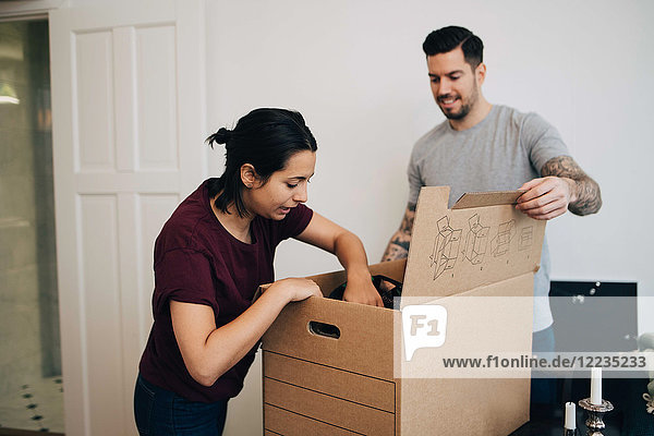 Man assisting woman in unpacking box at new house