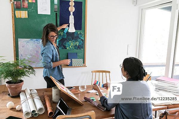 Weibliche Designprofis arbeiten im Home-Office zusammen.