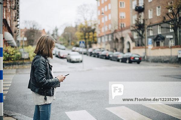 Seitenansicht des Mädchens mit dem Handy im Stehen auf der Stadtstraße