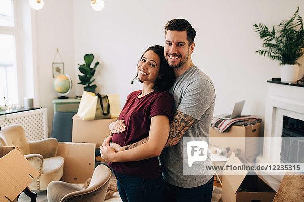 Lächelnder Mann  der schwangere Frau umarmt  während er im Wohnzimmer gegen Kisten steht.