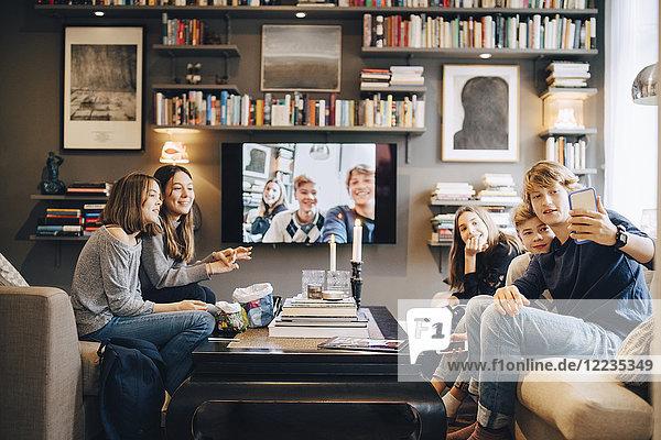 Männliche und weibliche Freunde  die zu Hause auf dem Sofa sitzen und Selfie nehmen