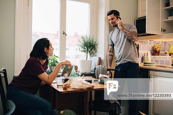 Frau schaut den Mann an  der auf dem Handy in der Küche spricht.