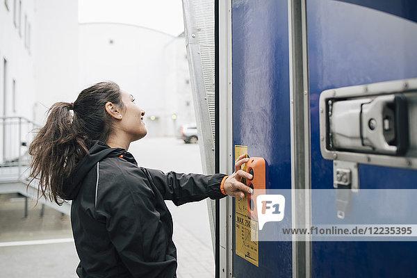 Frau schaut weg  während sie am Lieferwagen Knöpfe drückt.