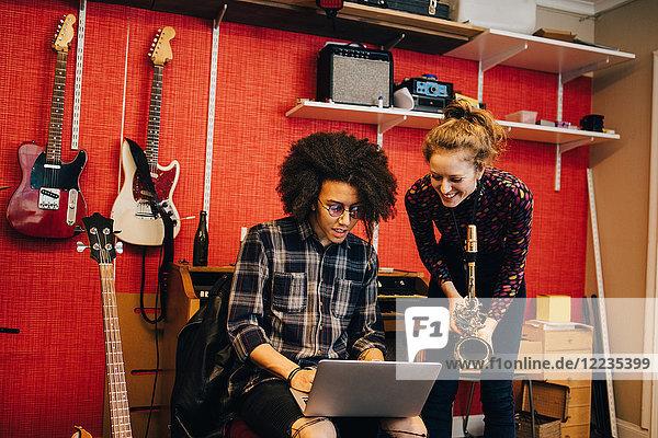 Frau mit Saxophon  die den Mann beim Üben im Tonstudio mit dem Laptop ansieht.