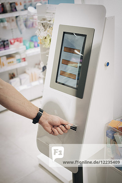 Cropped hand of male customer using kiosk at pharmacy store