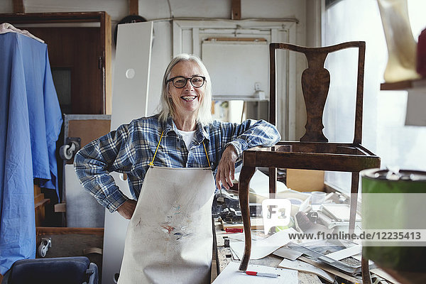 Portrait of smiling female standing by wooden chair at workbench