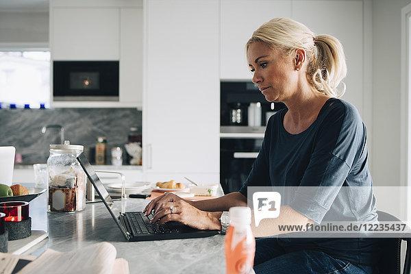 Seitenansicht der reifen blonden Frau mit Laptop auf der Kücheninsel