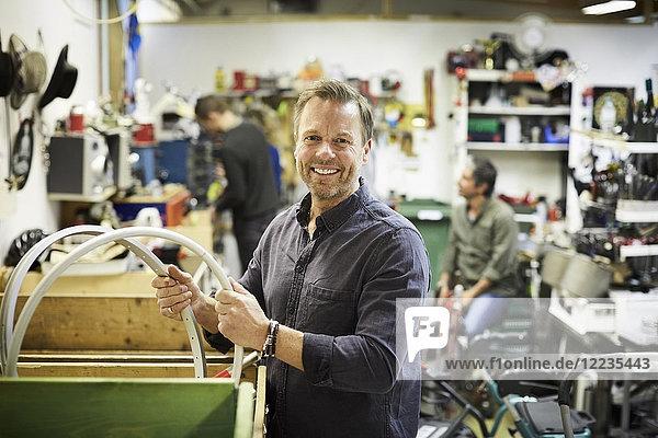 Porträt eines lächelnden reifen Freiwilligen  der gegen Kollegen in der Werkstatt arbeitet.