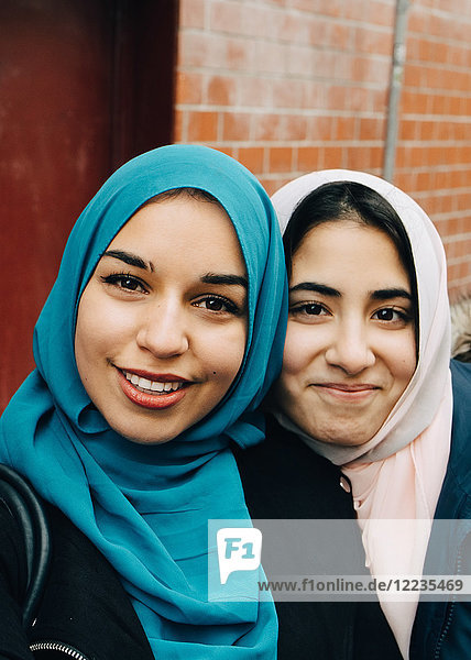 Portrait of smiling young woman taking with teenage friend against building in city