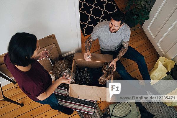 Hochwinkelansicht der Auspackbox von Mann und Frau im Wohnzimmer