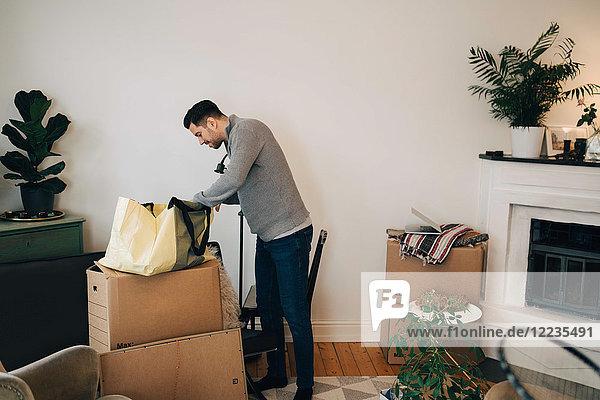 Mann sucht im Sack  während er im Wohnzimmer an der Wand steht.
