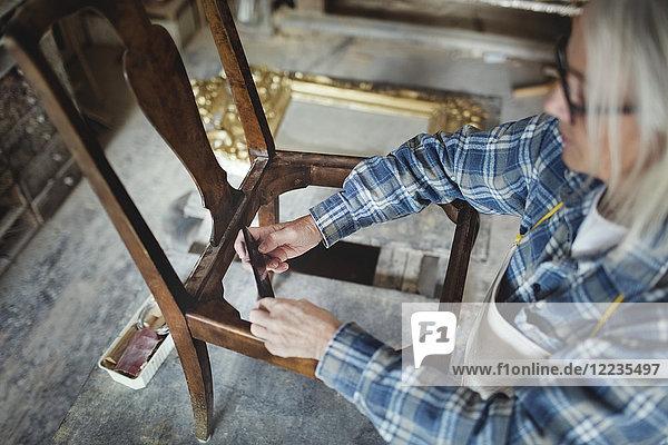 Hochwinkelansicht des Handwerkers  der in der Werkstatt Holzstühle herstellt. Hochwinkelansicht des Handwerkers, der in der Werkstatt Holzstühle herstellt.
