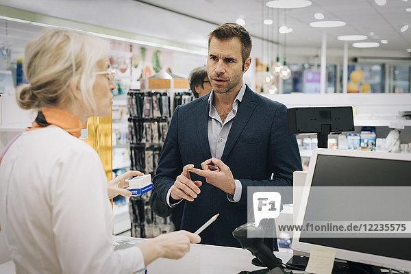 Reifer Mann erklärt Apothekerin an der Kasse im Sanitätshaus