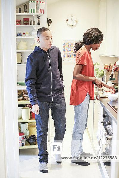 Volle Länge des Teenagers  der von der Mutter beim Kochen in der Küche spazieren geht.