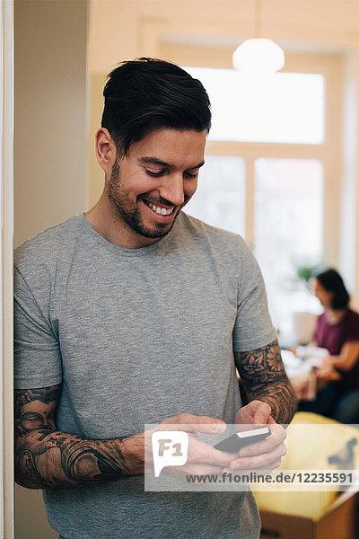 Lächelnder Mann  der sein Handy benutzt  während er sich an die Tür des neuen Hauses lehnt.