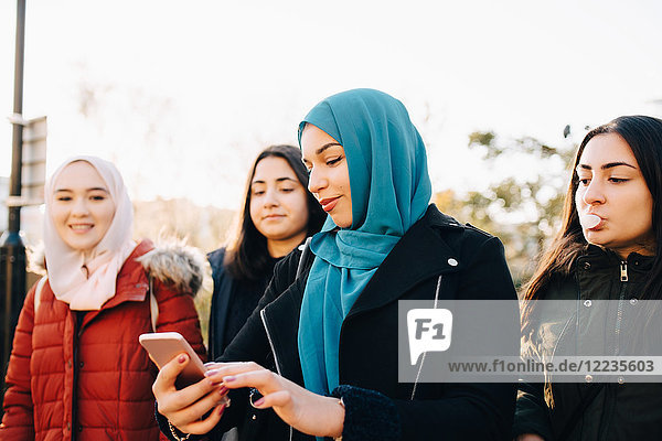 Young Muslim woman using smart phone while standing with female friends against sky