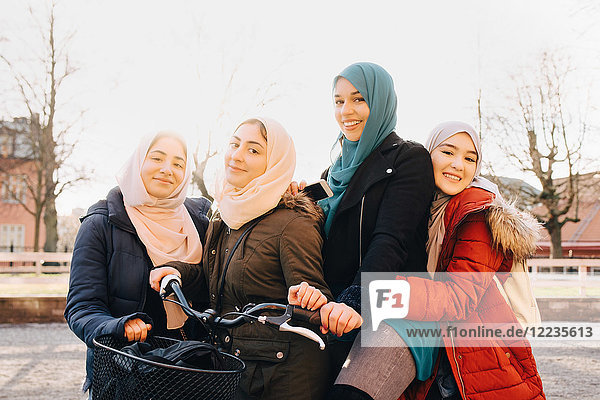 Portrait of happy multi-ethnic female Muslim friends with bicycle in city against sky