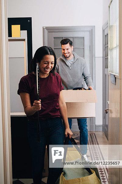 Lächelndes Paar mit Box und Tasche beim Gehen im Flur zu Hause