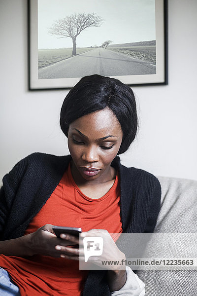 Mid adult woman using smart phone on sofa at home