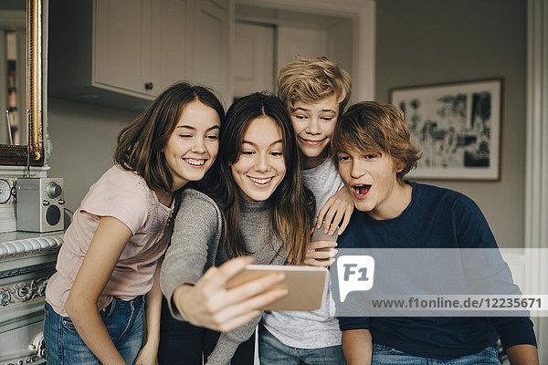 Fröhliche Freunde nehmen Selfie durch Smartphone  während sie zu Hause stehen.