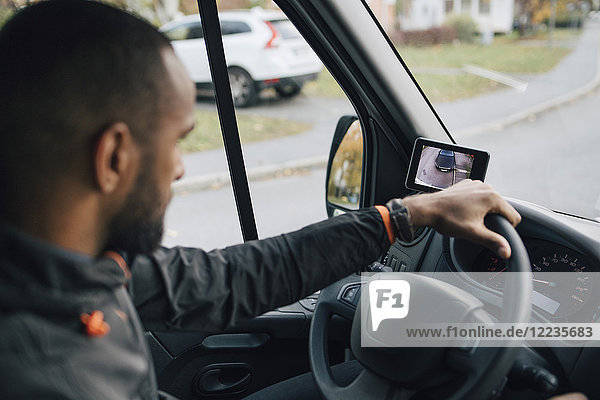 Männlicher Arbeiter schaut auf den Bildschirm des Geräts  während er einen Lieferwagen in der Stadt fährt.