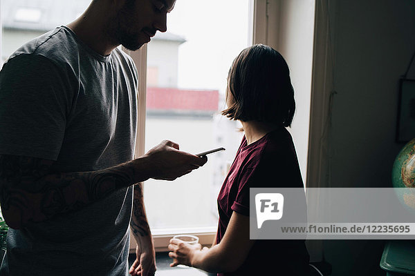 Frau schaut durchs Fenster  während der Mann zu Hause mit dem Handy telefoniert.