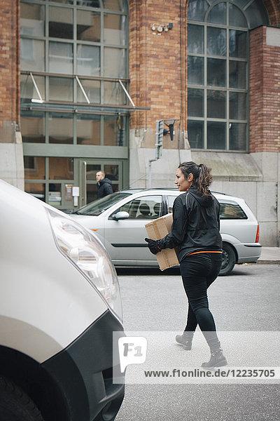 Volle Länge des weiblichen Botenkastens beim Überqueren der Straße inmitten von Autos in der Stadt