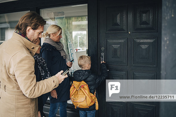 Rückansicht des Entriegelungskombinationsschlosses an der Haustür durch die Familie