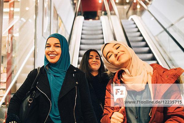 Portrait of happy female friends on escalator in shopping mall