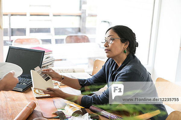 Geschäftsfrau im Gespräch mit Kollegin bei Tisch im Home-Office
