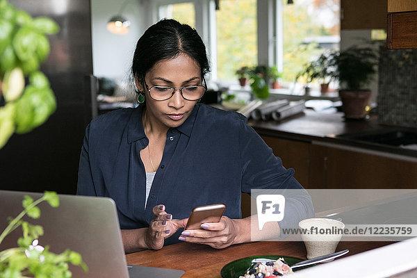 Geschäftsfrau mit Handy und Laptop auf dem Tisch im Home-Office