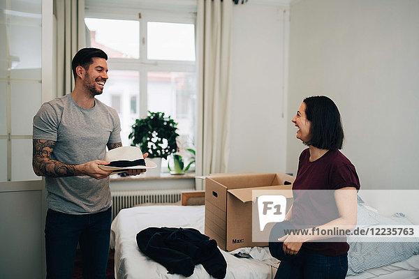 Fröhlicher Mann mit Hut im Gespräch mit einer Frau  die zu Hause am Bett faltet.