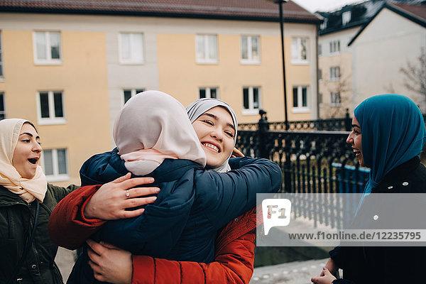 Happy Muslim women embracing by friends in city