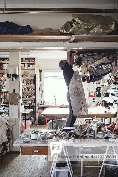 Männlicher Besitzer sucht in der Werkstatt nach gerollten Stoffen Männlicher Besitzer sucht in der Werkstatt nach gerollten Stoffen