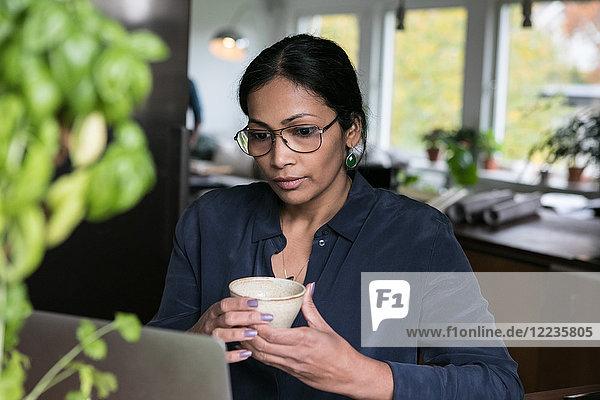 Geschäftsfrau hält Tasse beim Blick auf Laptop im Home-Office