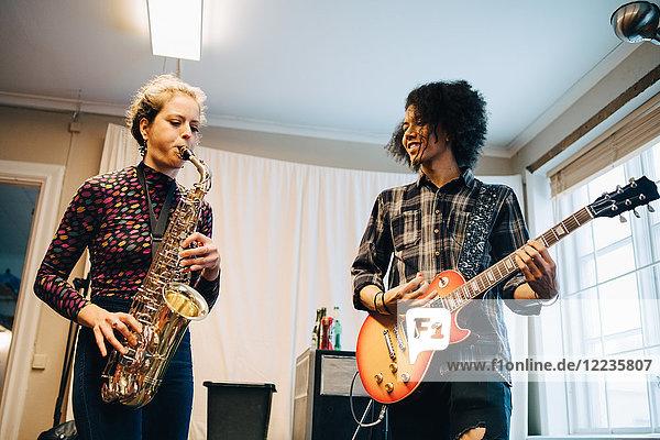Freunde  die Saxophon und Gitarre spielen  während sie im Aufnahmestudio üben.