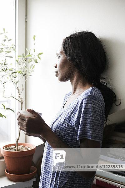 Seitenansicht einer erwachsenen Frau  die eine Kaffeetasse hält  während sie sich zu Hause an die Wand lehnt.