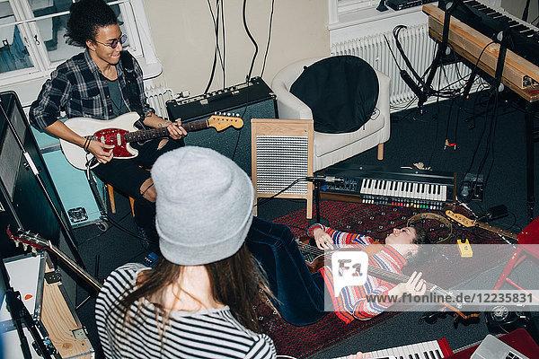 Hochwinkelansicht von Gitarrenspielern und -freunden während der Proben im Studio
