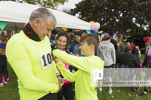 Familienläufer  die Marathon-Lätzchen befestigen und sich auf einen Wohltätigkeitslauf im Park vorbereiten.