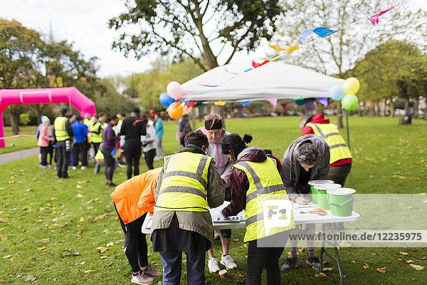 Freiwillige überprüfen Läufer beim Charity-Lauf im Park