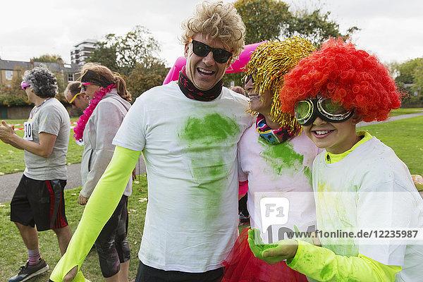 Portrait verspielte Läufer in Perücken und Urlaubspulver beim Charity-Lauf im Park