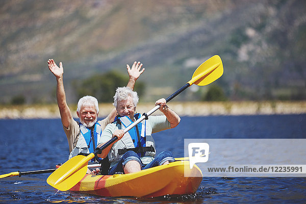 Verspieltes  tatkräftiges Kajakfahren auf dem sonnigen Sommersee